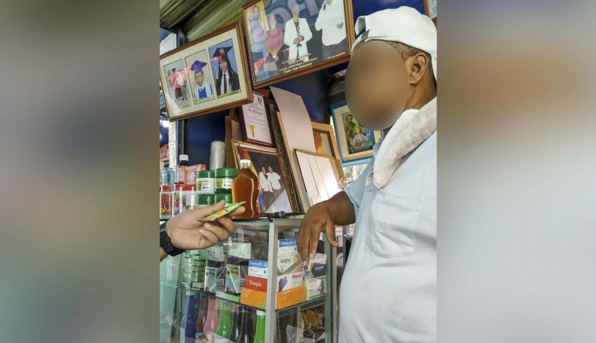 Un vendedor entrega un sobre de Quenopodio a un cliente del local naturista.