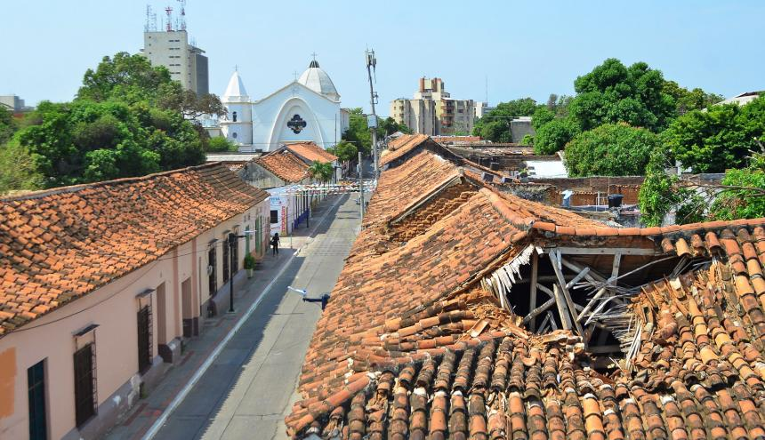 En primer plano, una casa deteriorada. Al fondo, la catedral Nuestra Señora del Rosario.