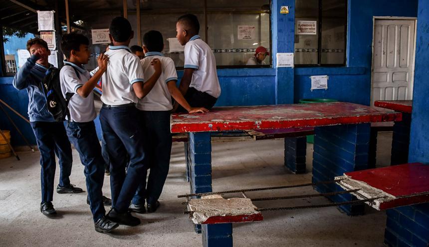 Estudiantes hacen fila para almorzar en el comedor del colegio en mal estado.