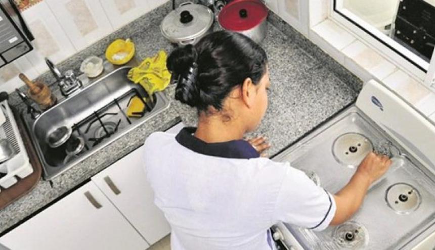 Trabajadora doméstica  hace labores en una cocina.