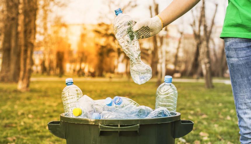 Una persona realiza recolección de botellas plásticas para reciclaje en un parque de la ciudad.