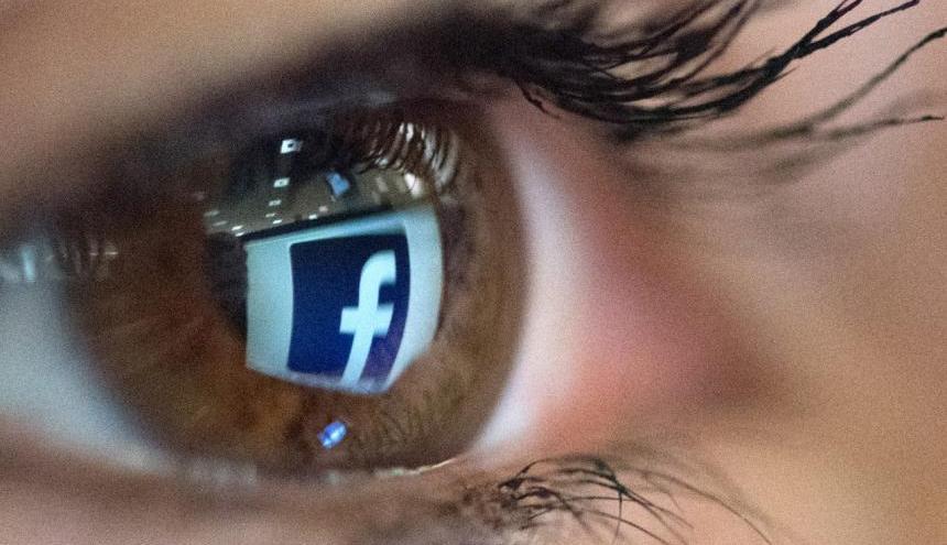 Una persona ve el logotipo de Facebook que se refleja en sus ojos. Imagen de referencia.