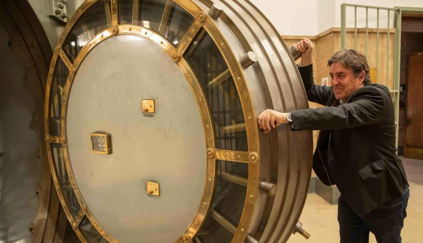 García Montero posa junto a la puerta acorazada de la bóveda de seguridad del antiguo banco donde hoy funciona el Instituto Cervantes.
