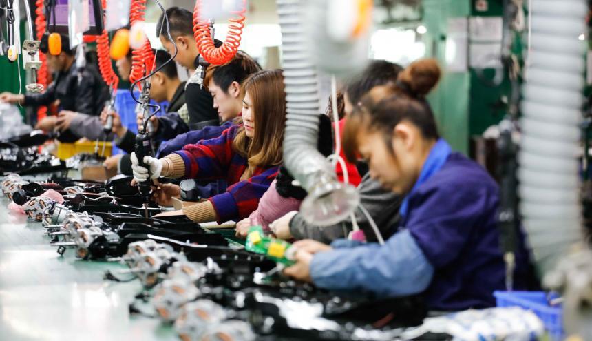 Trabajadores en una industria china en Jiuajing elaboran y producen aparatos electrónicos.