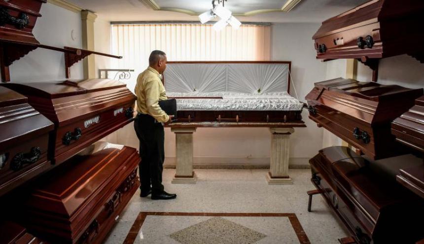 Un funcionario de una funeraria local muestra un ataúd en una de las sedes de la compañía en Barranquilla.