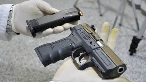 Un detective del Laboratorio de Criminalística de la Policía sostiene una pistola 9 milímetros en sus manos.