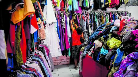 4c31168009 Una mujer busca entre la ropa colgada en uno de los establecimientos que se  dedican a comercializar ropa de segunda mano