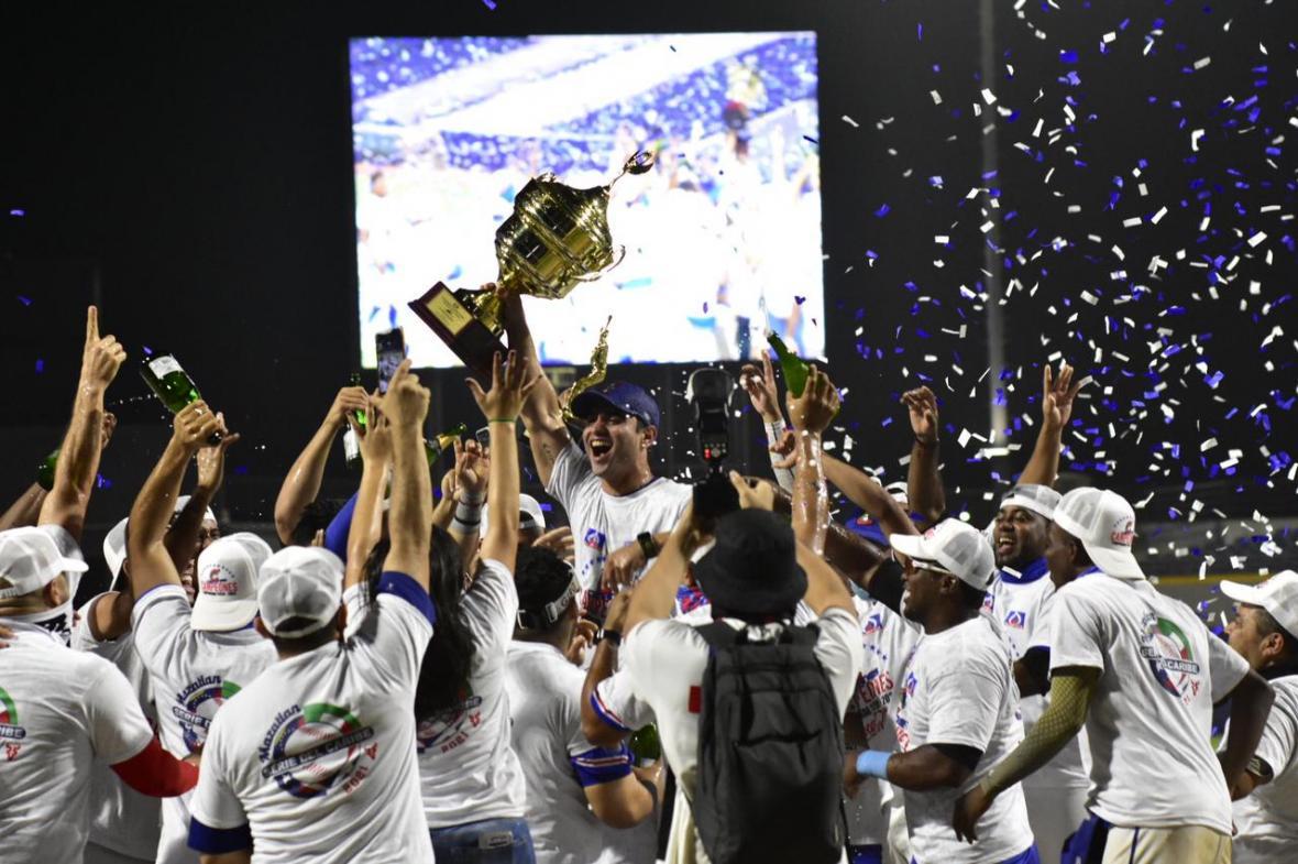 Los jugadores de Caimanes celebran con el mánager José Mosquera cargando el trofeo 2020-2021.