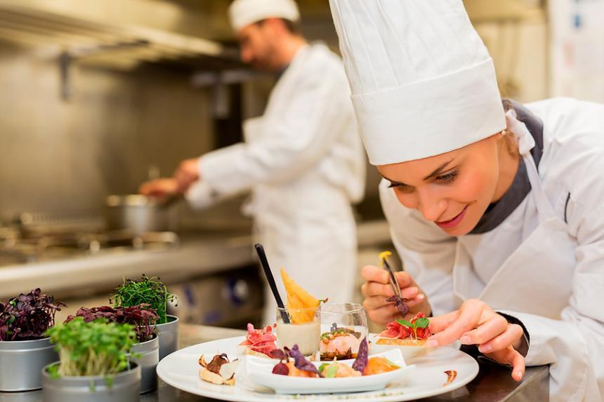 Una Chef Ensambla, Con Suma Delicadeza, Un Plato De Alta Cocina.  Shutterstock