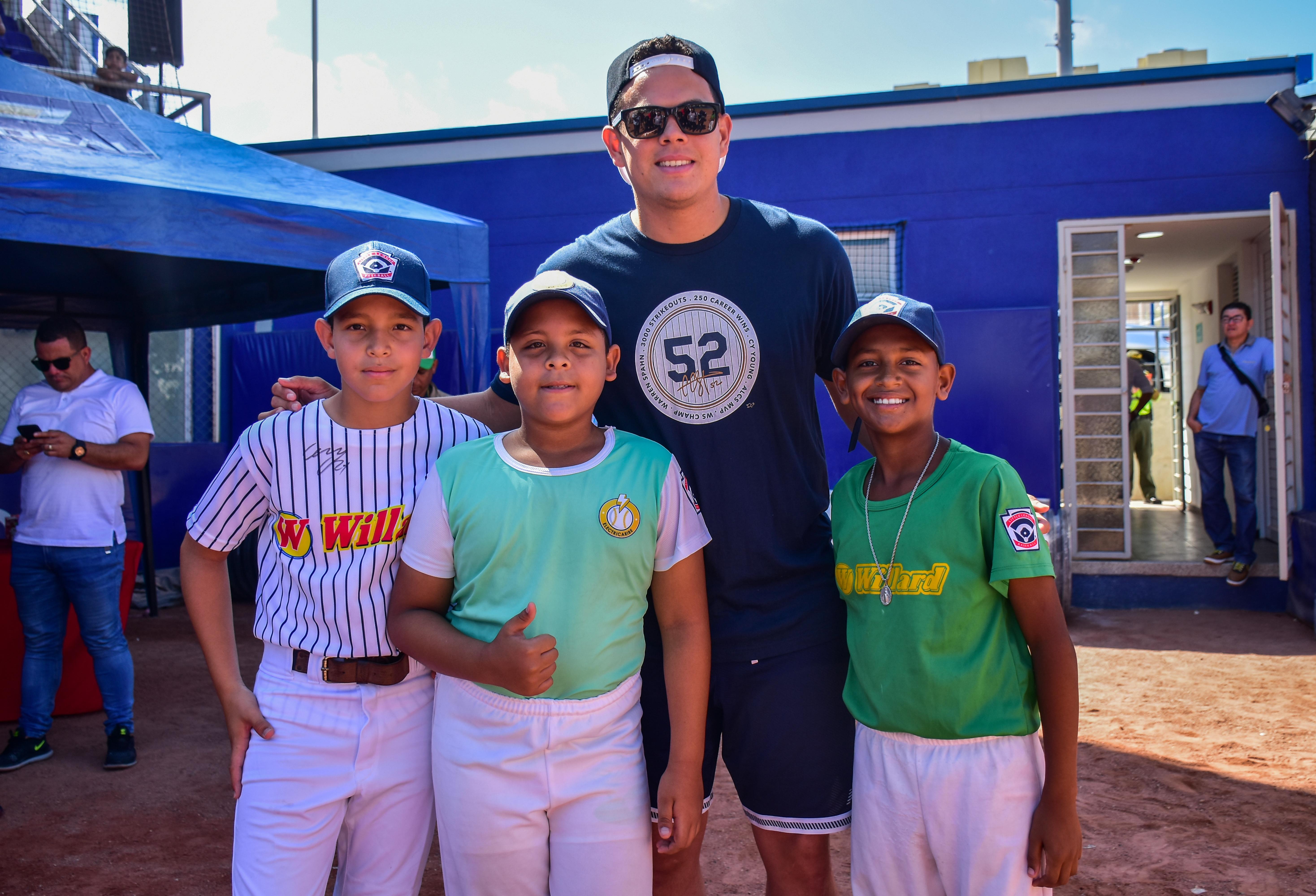 Los pequeños peloteros Andrés Urueta, Alberto Molina y Keiner De la Peña junto a Giovanny Urshela.