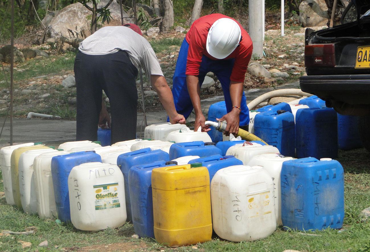Hombres llenan pimpinas con agua de una manguera.