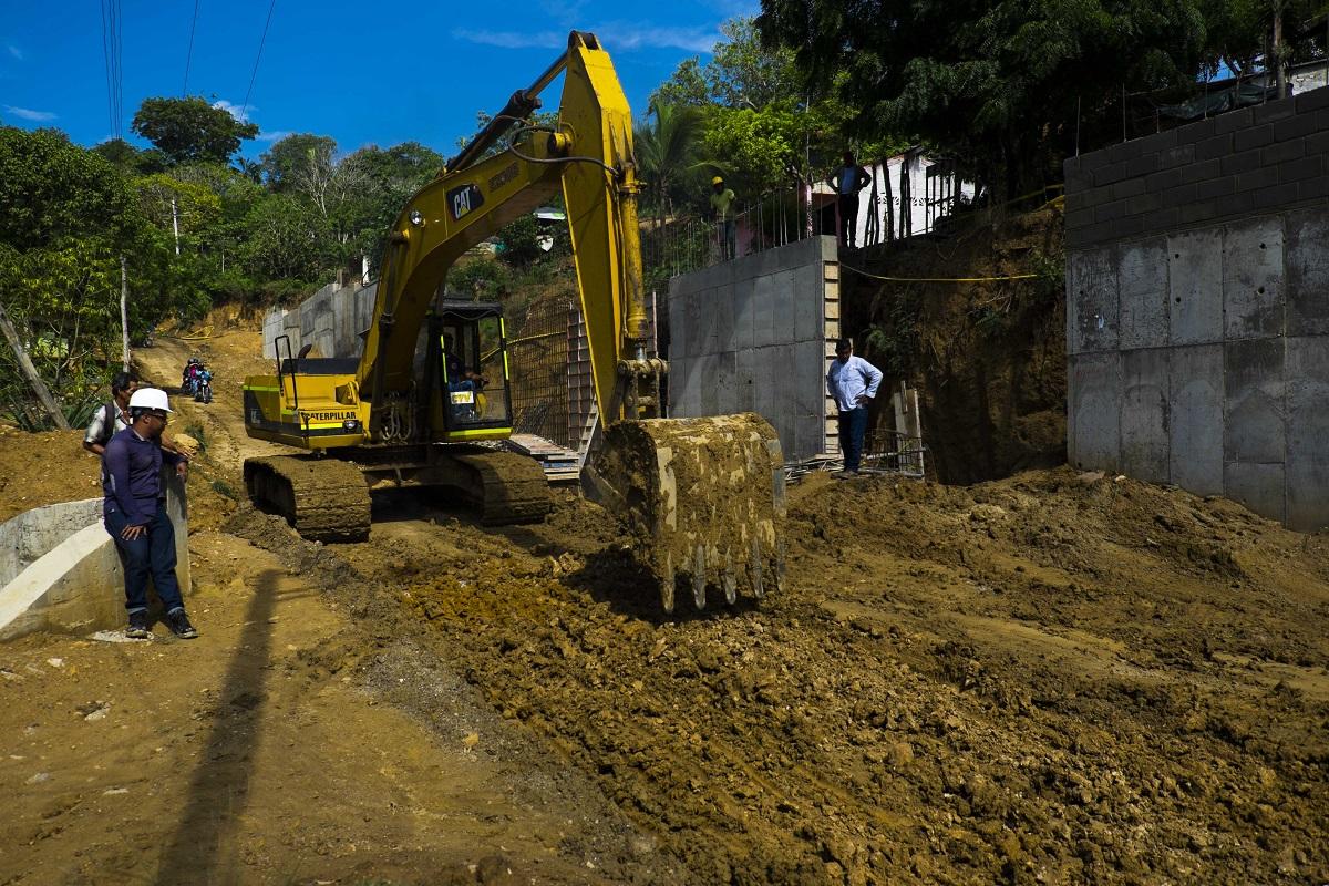 Un obrero supervisa el trabajo de la maquinaria en la construcción de la vía.