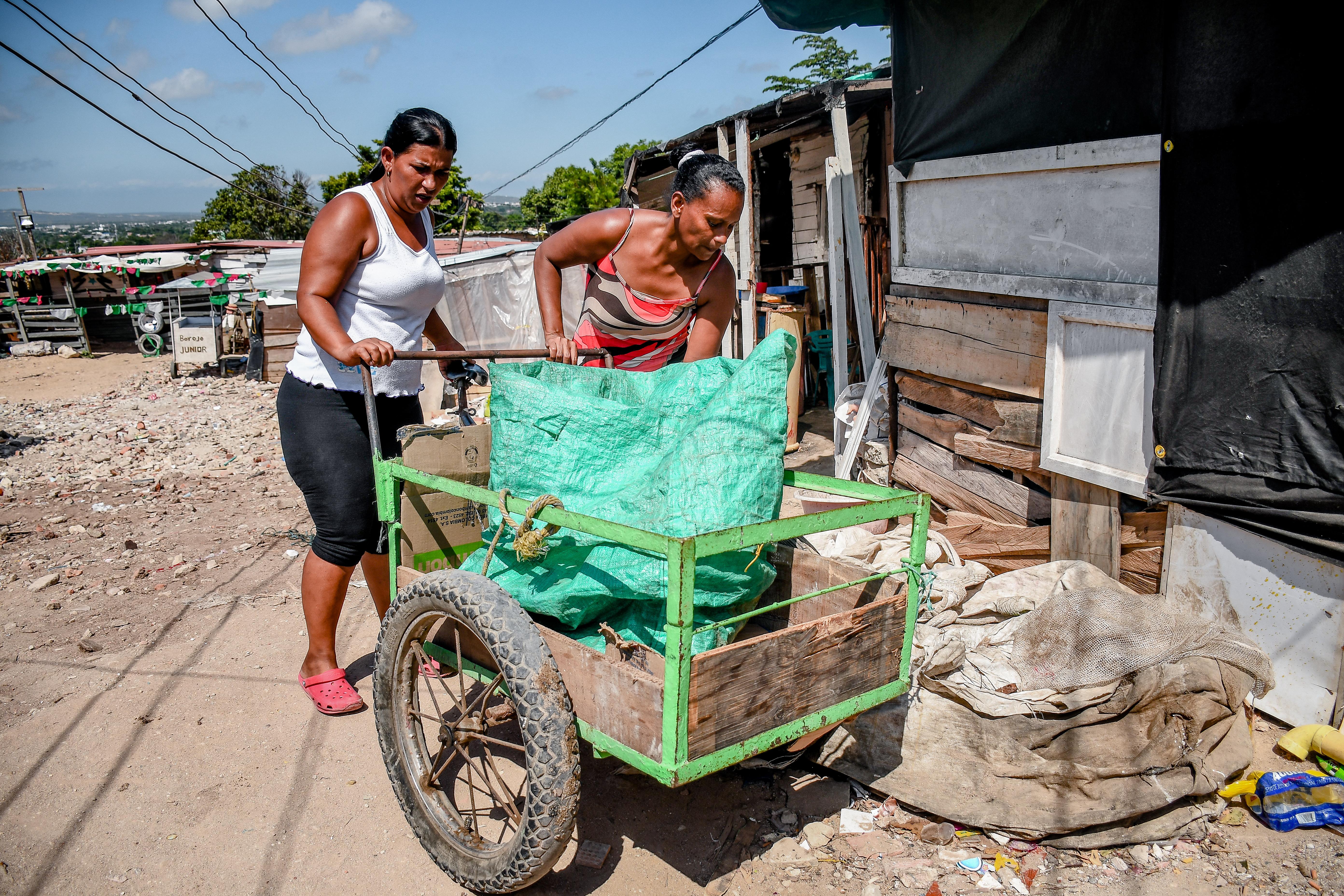 Dos mujeres de este sector maniobran uno de los coches de madera en los que reciclan todas las noches.