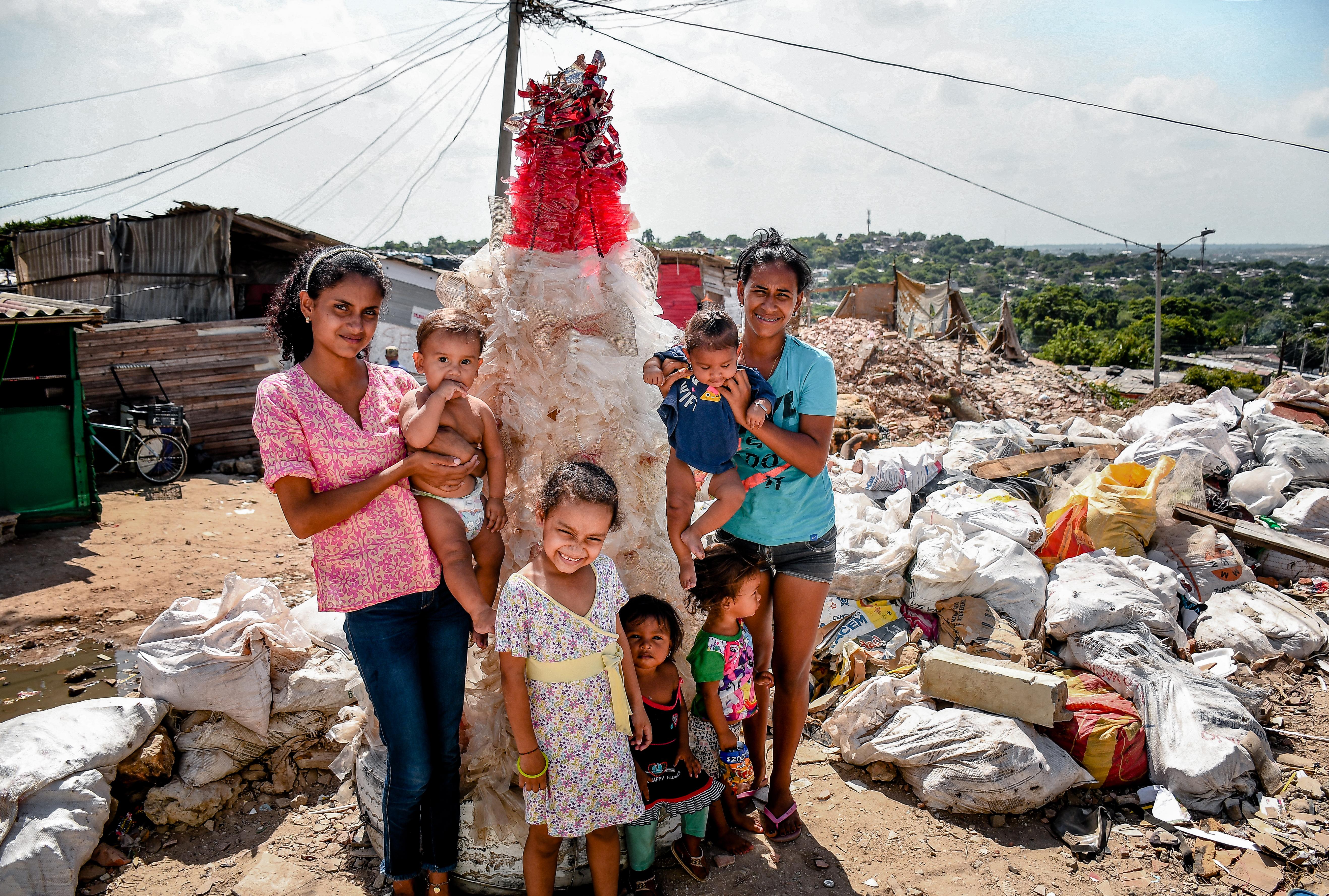 Dos mujeres, junto a sus hijas, posan junto al árbol de bolsas plásticas y cables, en Villa Caracas.