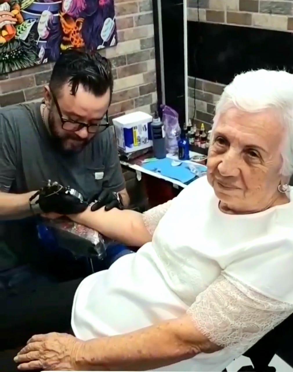 Alejandro Botero tatuando a Maya en su local.