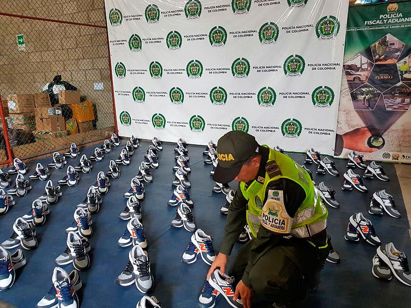 Un policía arregla parte de los 85 pares de zapatos deportivos decomisados.